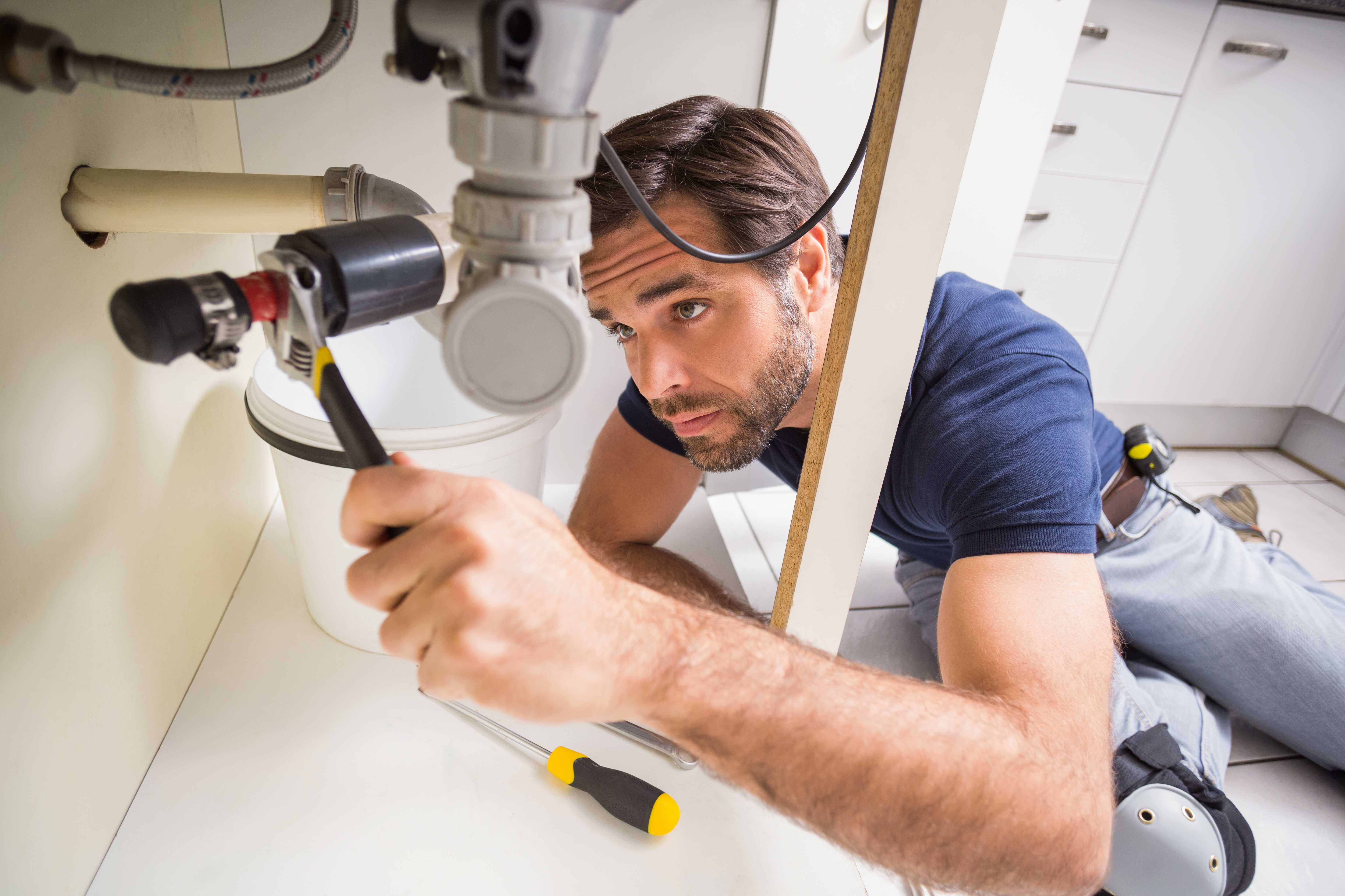 A Plumber Fixing a Pipe