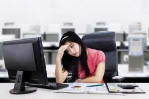 A tired woman sitting at her desk in work