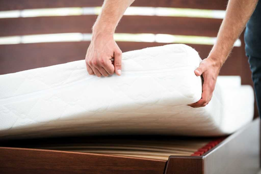 Young Man Checking the Quality of Mattress