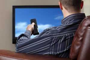 A man watching television while sitting on a sofa