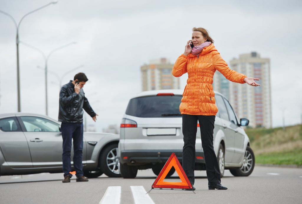 Man and woman on phone with car accident in the background