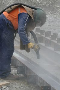 man sandblasting metal beams