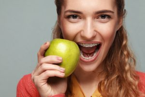 Woman with braces holding fruit