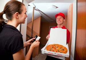 delivery man bringing pizza to customer's doorstep