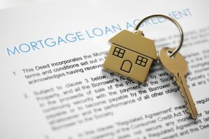 Mortgage loan agreement with house key chain and key on top