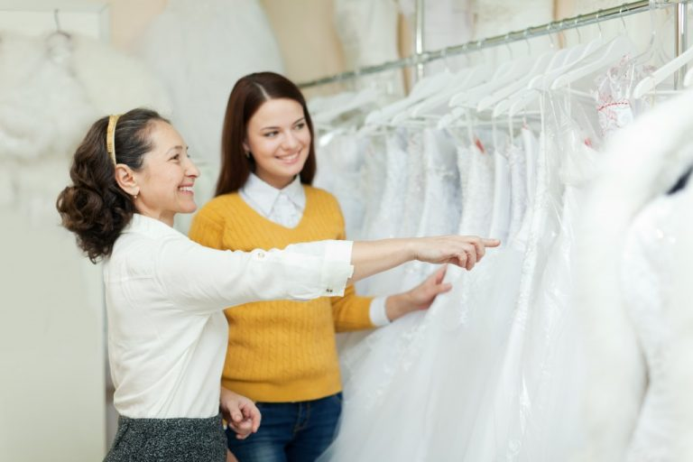 Bride-to-be being assisted in choosing a wedding dress