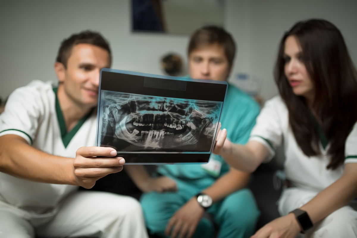 Group of dentists examining x-ray of teeth