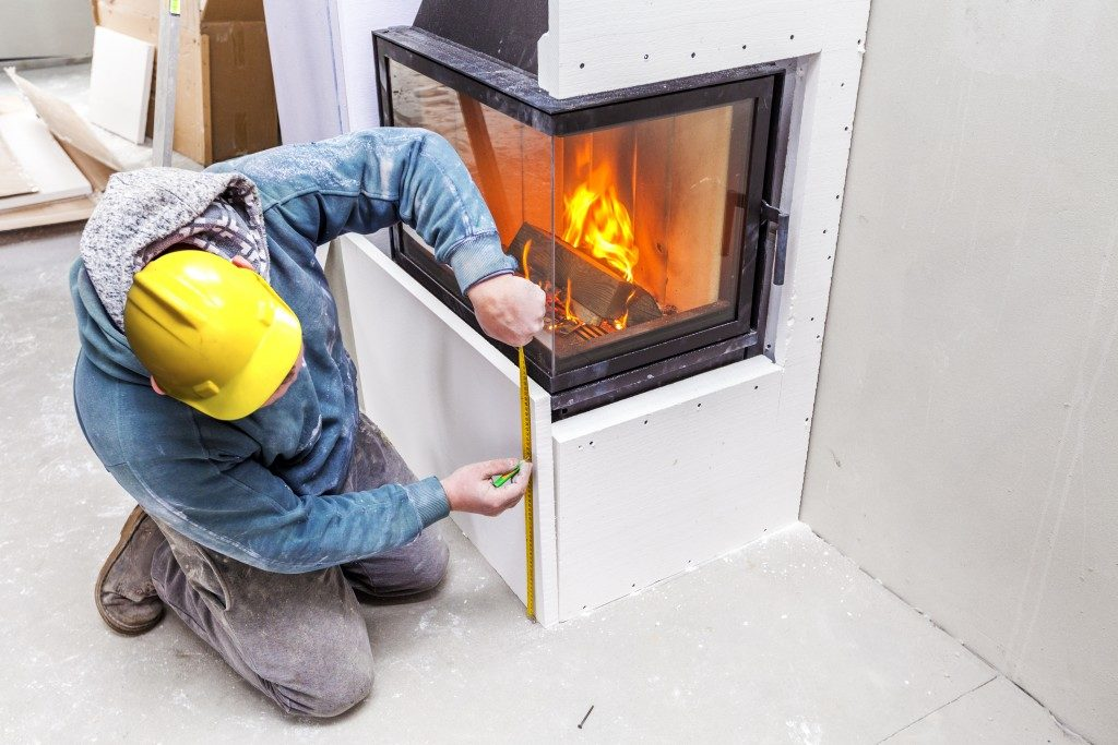 man measuring installed fireplace