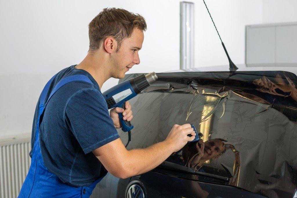 Worker applying a tint film on a car window