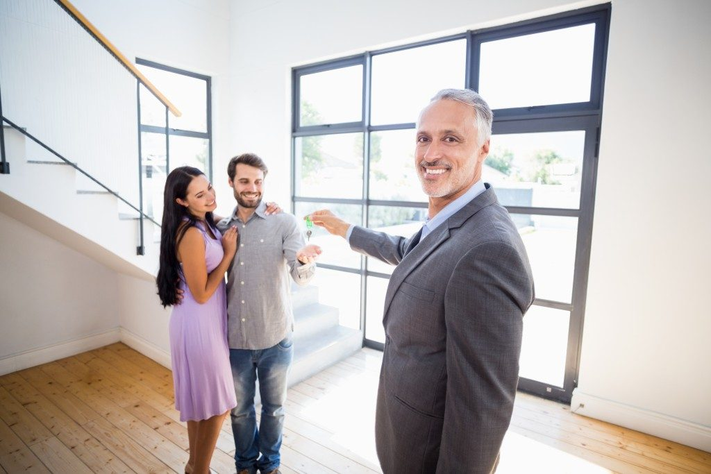 Real Estate agent handing key over