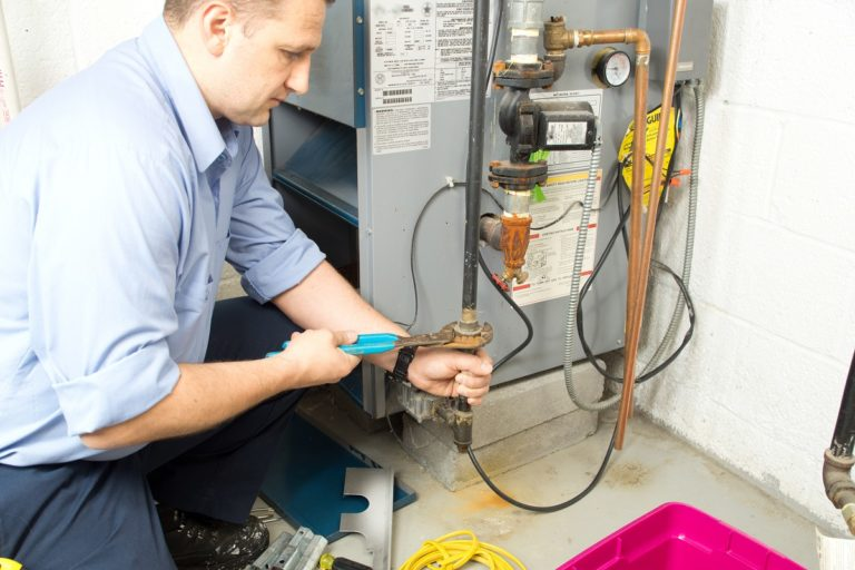 Plumber fixing a furnace