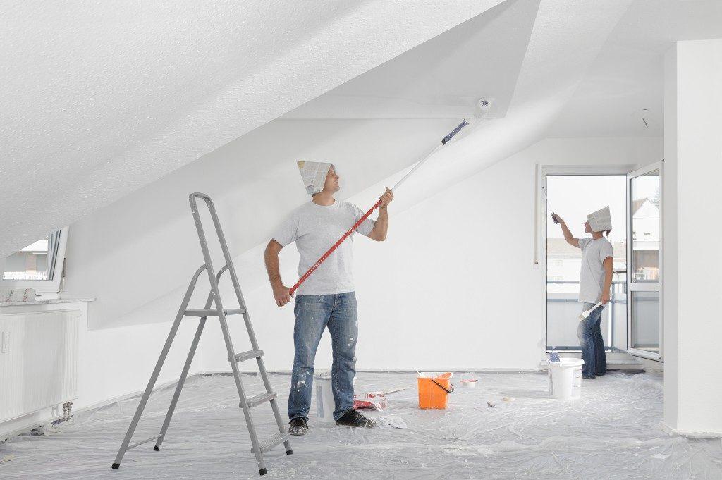 men repainting attic