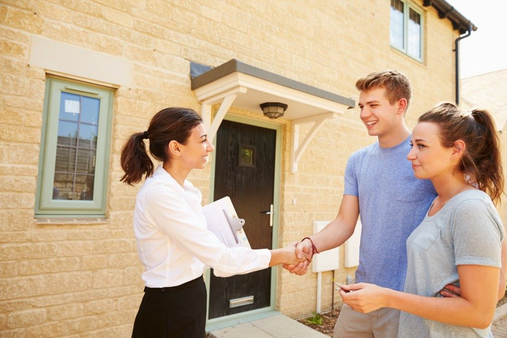 Agent shaking the hand of the new house owner