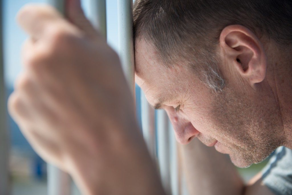 Depressed male inmate holds prison bars
