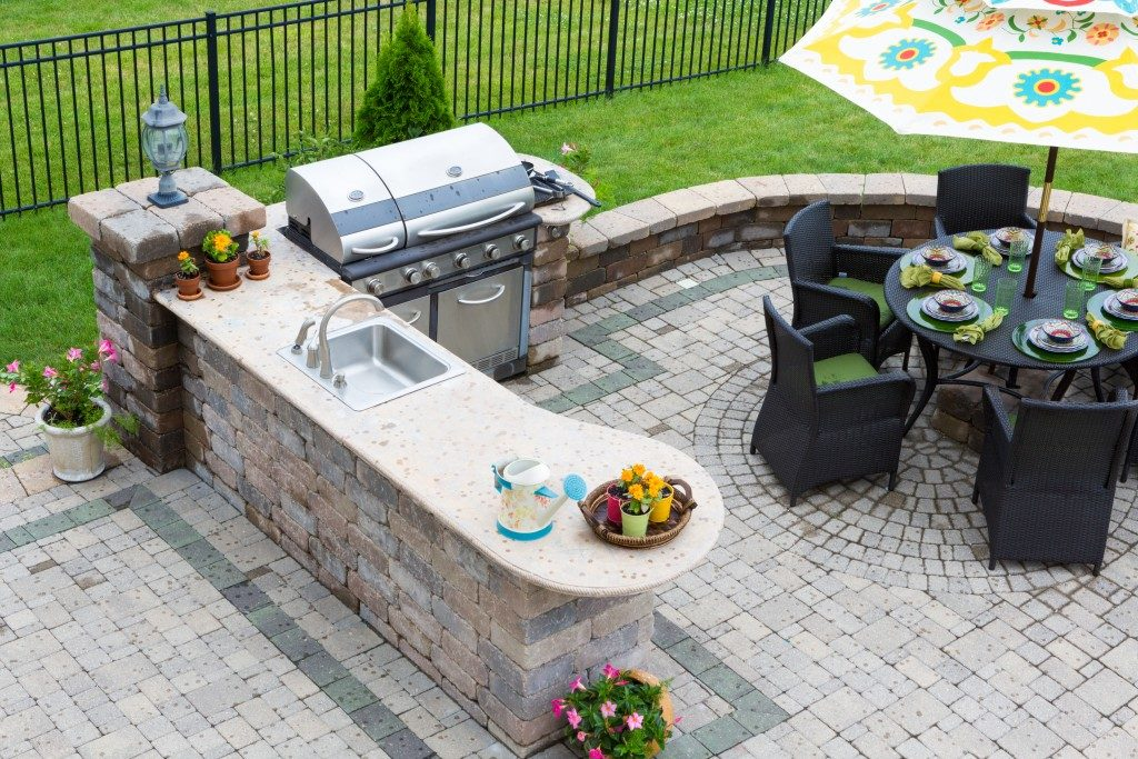 High angle view of a stylish outdoor kitchen, gas barbecue and dining table set for entertaining guests with formal place settings and flowers on a paved patio