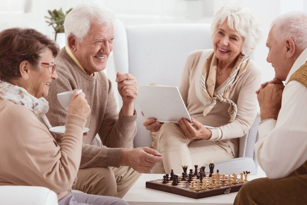 elderly peoplehaving coffee and playing chess