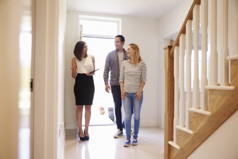 couple checking out a house with real estate agent