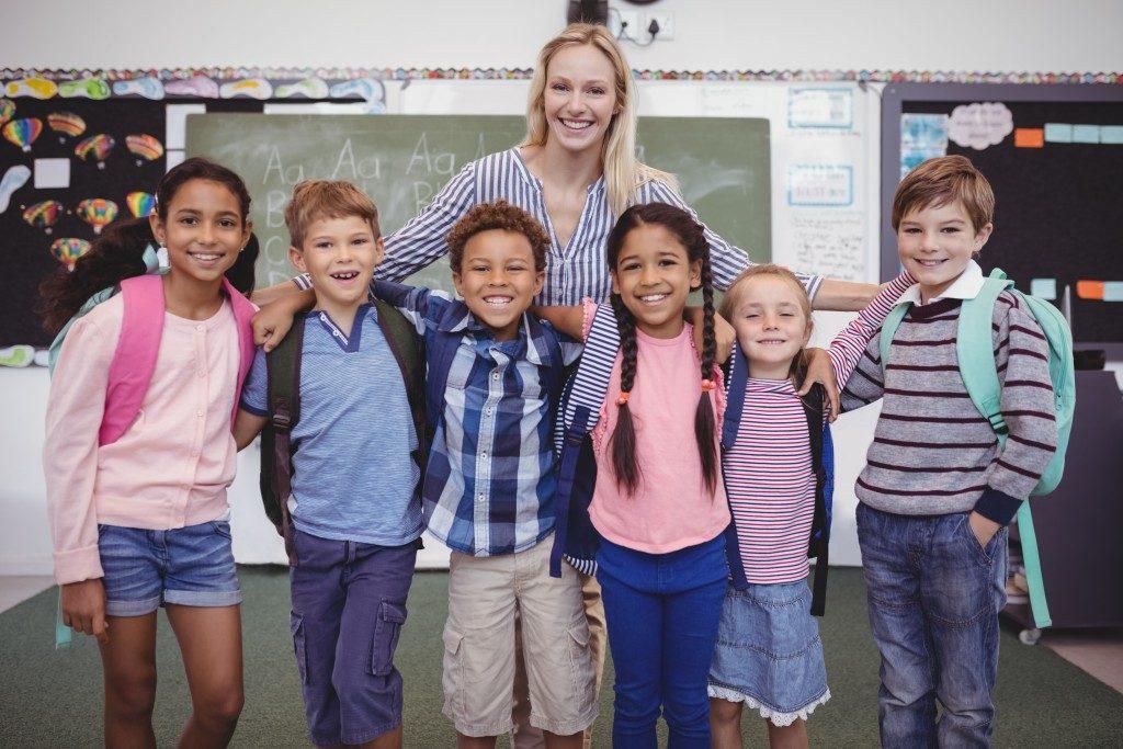 Kids posing with their teacher
