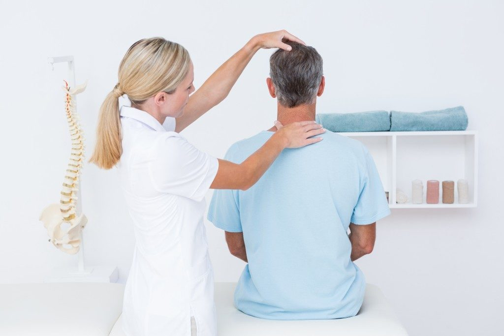 Doctor checking neck in medical office