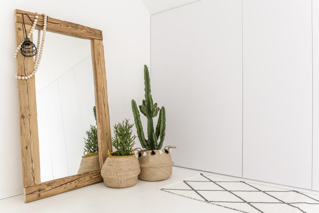 white room with wooden full-sized mirror and plant on baskets