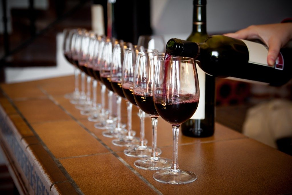wine bottle pouring a row of glasses for tasting