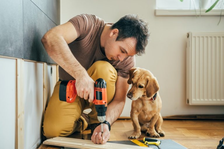 Man building something with his dog