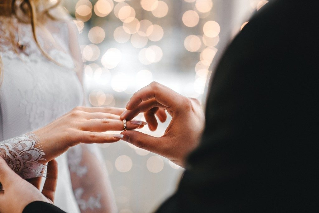groom putting a ring on his bride
