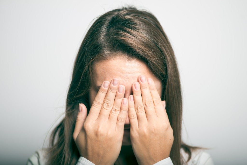 worried woman covering her face