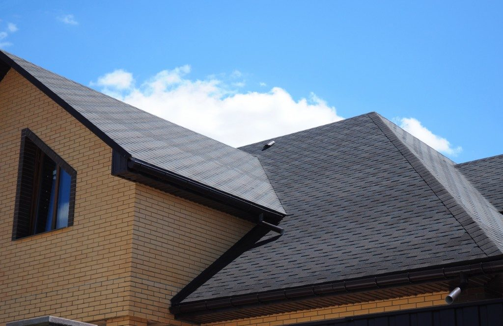 Grey roofing with black gutters and brick-wall house