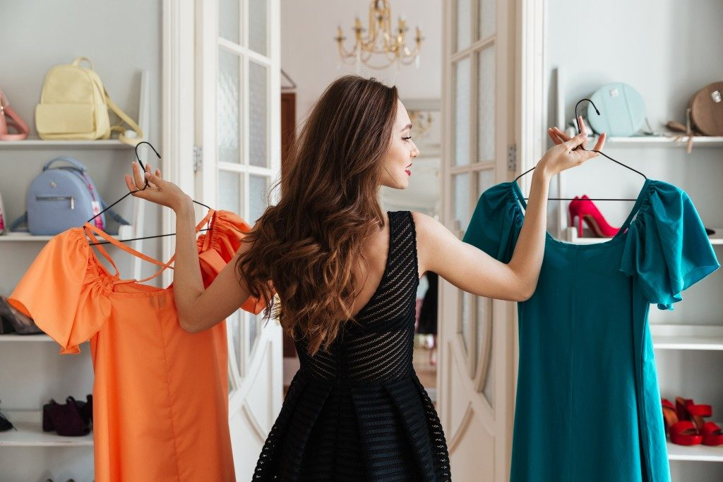 woman choosing which dress to wear