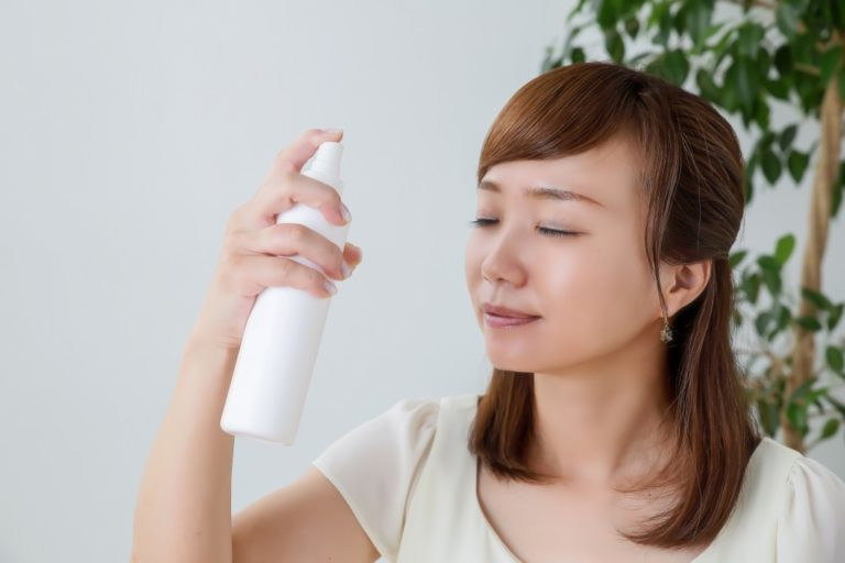 Asian woman spraying her face with skincare product