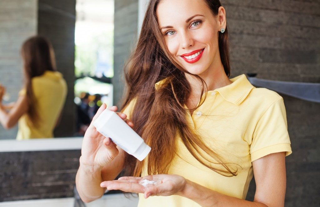 Woman applying shampoo on her hair