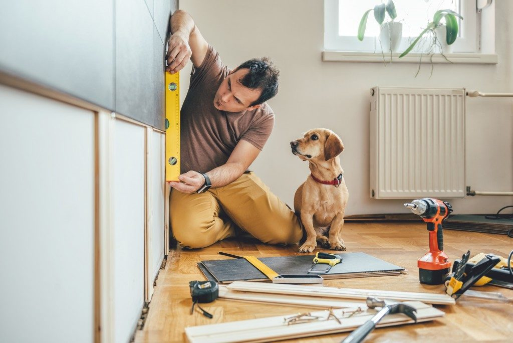 man doing construction work at home with his dog