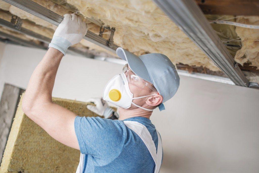 man installing insulation in a garage