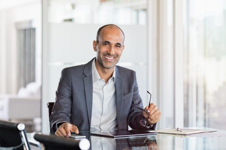 Business man holding glasses in modern office