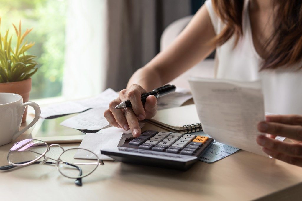 Woman computing her bills with a calculator