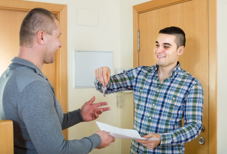 man handing keys and contract to renter