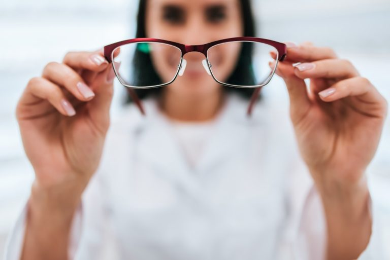 woman holding a pair of eyeglass
