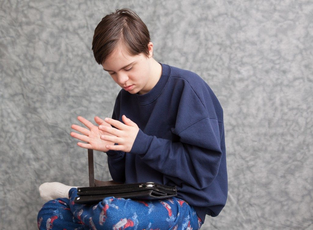 horizontal orientation of a boy with autism and down's syndrome clapping his hands as he plays with a tablet device / Apps for children with Autism