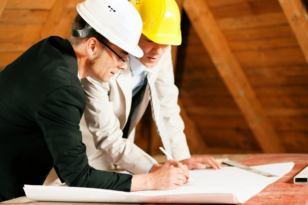 architect and contractor working on plan of house