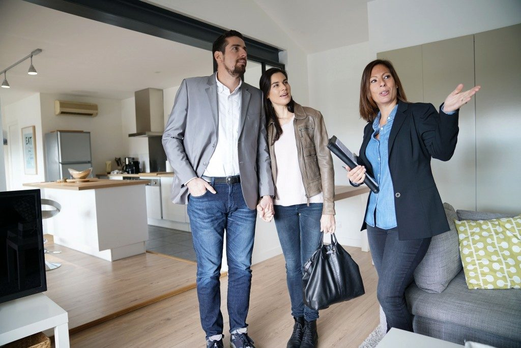 couple with real estate agent at house viewing
