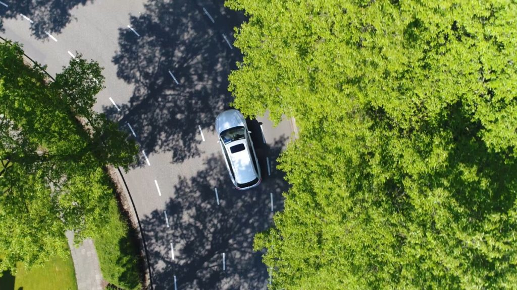 car being followed by a drone from above