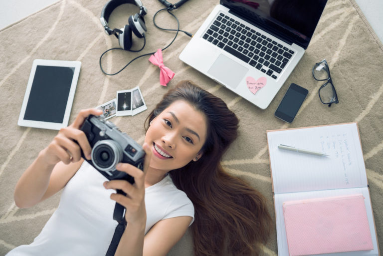 woman holding a camera along with her gadgets