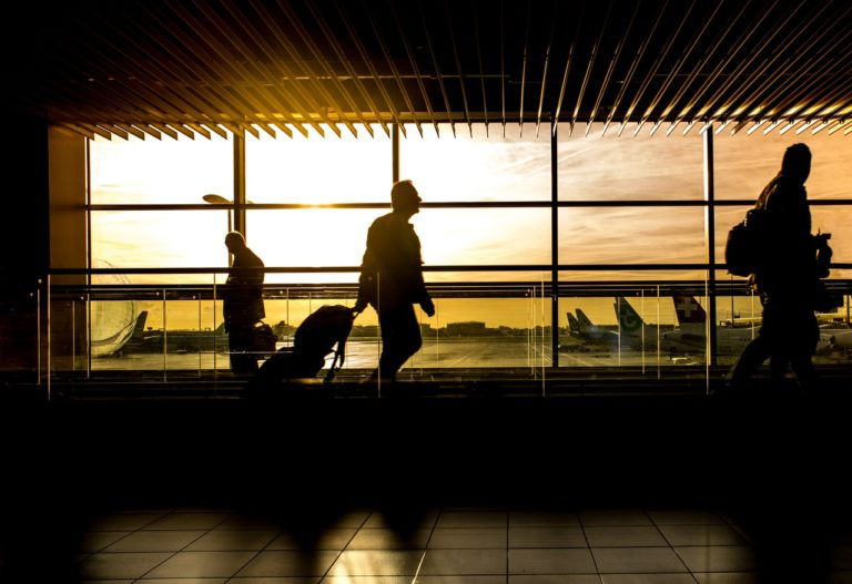 airport terminal with silhouette of people walking through