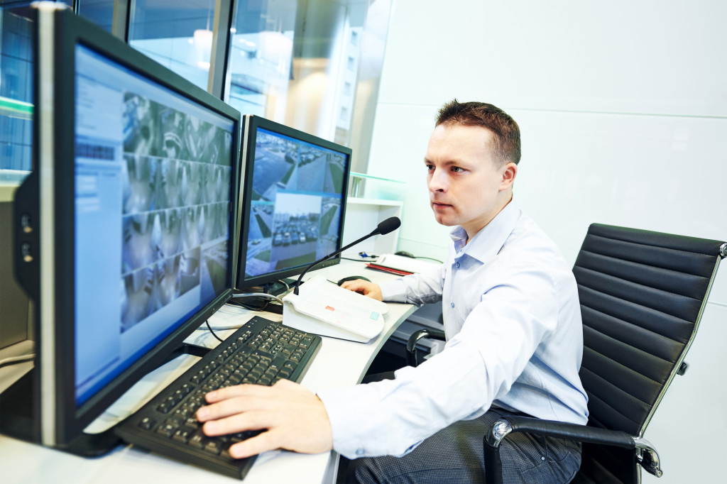 man watching security camera feed
