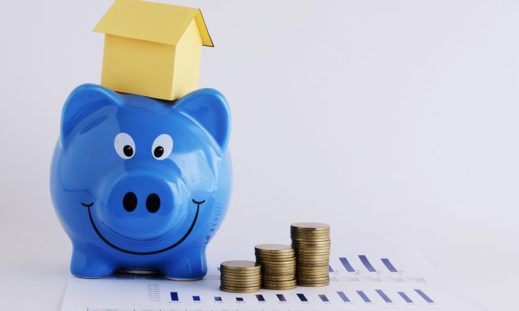 Pile of coins, a piggy bank and a miniature house