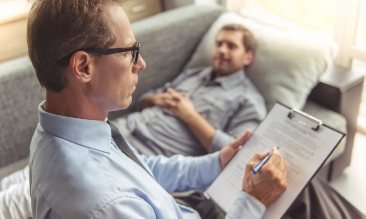 Man telling about his problems while lying on the couch at the psychotherapist