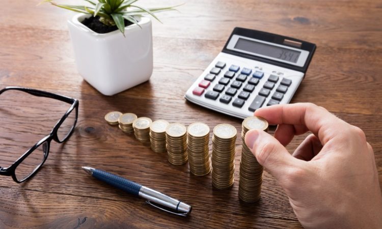 stacked coins, calculator and a pen