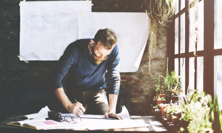 Man working standing up next to his desk