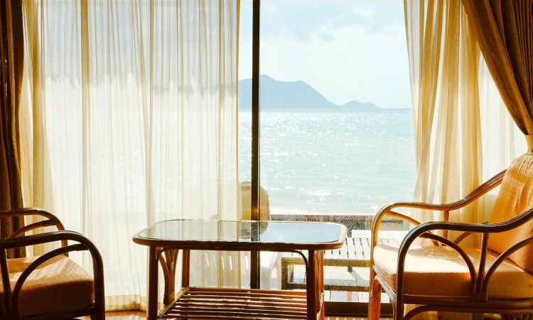 coffee table and chairs beside a glass window overlooking the sea
